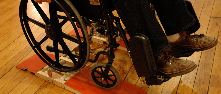 Ramps wheelchair DJ interface. A manual wheelchair sits on top of a roller system with red ramps.