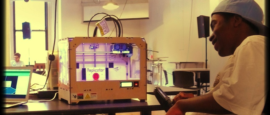 Young teen sitting in front of Makerbot 3D printer