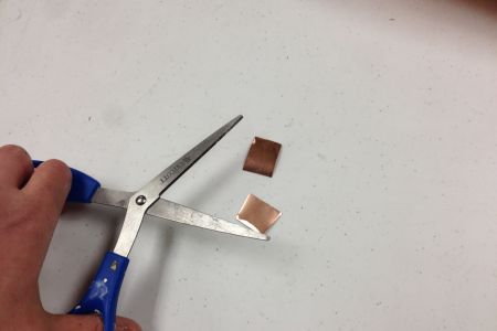 two small squares cut from previously cut copper rectangle