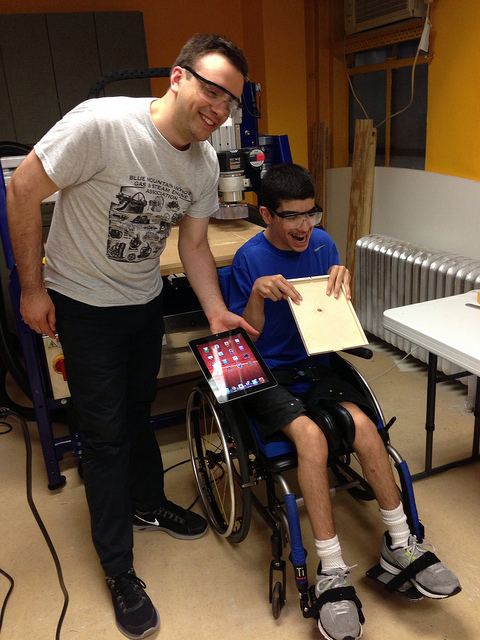 Two people in front of a CNC machine, man is standing and young man with CP is holding ipad holder he made.